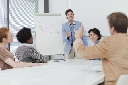 interrogations: Businessman raising hand in meeting LANG_EVOIMAGES