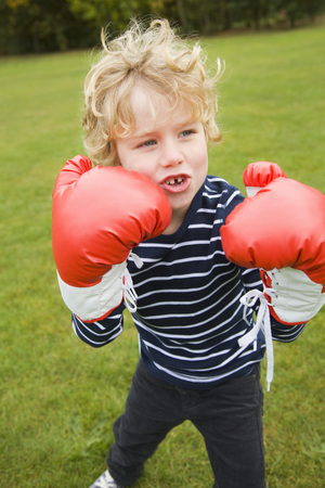boxing day: Boy playing with boxing gloves outdoors