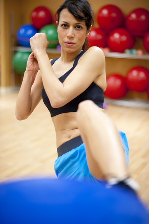 kicked out: Woman kick boxing in gym LANG_EVOIMAGES