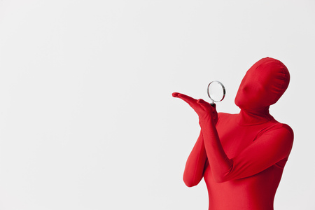 finding out: Woman in bodysuit with magnifying glass LANG_EVOIMAGES