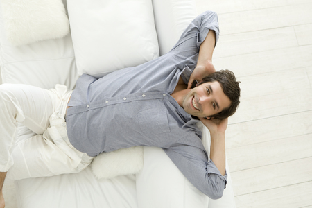 leans on hand: Smiling man relaxing on sofa LANG_EVOIMAGES