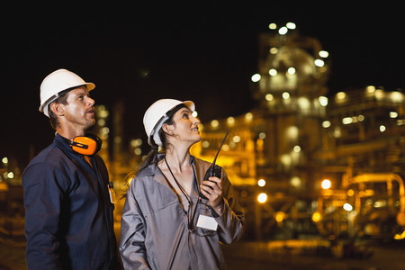 Workers talking at oil refinery LANG_EVOIMAGES