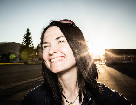 suns: Smiling woman and sun flare outdoors LANG_EVOIMAGES