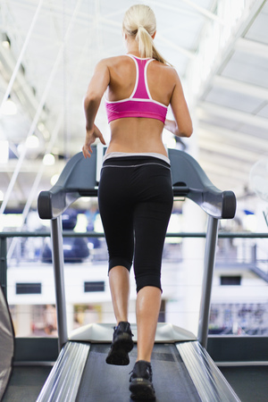 ascends: Woman using exercise machine in gym