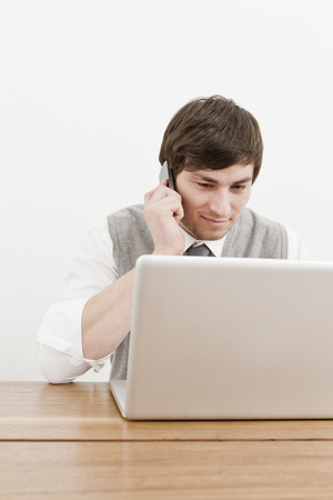 responding: Businessman using laptop and cell phone LANG_EVOIMAGES