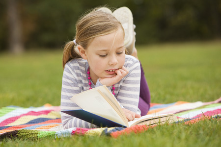 lays down: Girl reading book on picnic blanket