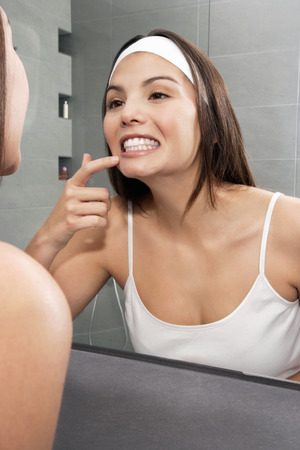 grooming: Woman examining her teeth in mirror LANG_EVOIMAGES