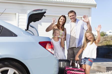 Family loading up car trunk for vacation