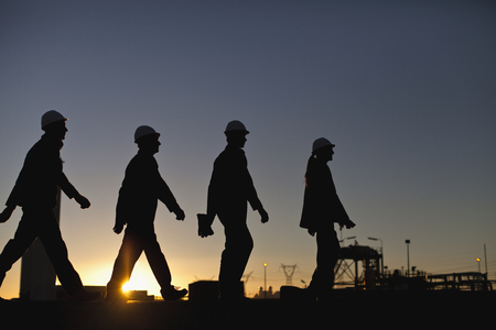 build in: Silhouette of workers at oil refinery