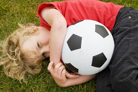 bashful: Boy holding soccer ball in grass LANG_EVOIMAGES