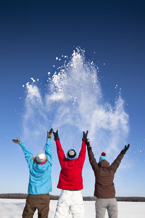 tosses: People playing with snow in field