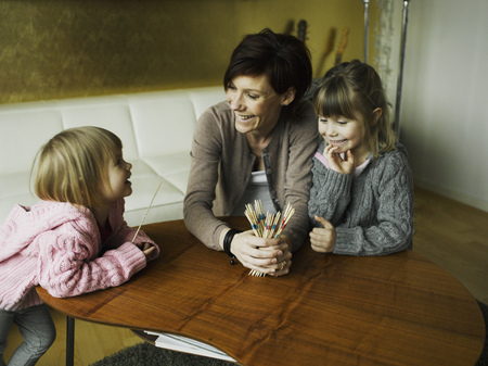 love seat: Mother and daughters playing together