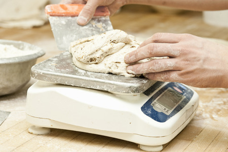 Baker weighing dough in kitchen LANG_EVOIMAGES