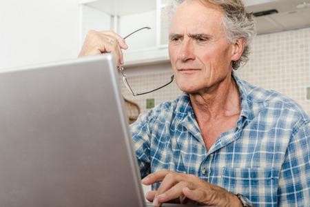 studied: Older man using laptop in kitchen LANG_EVOIMAGES