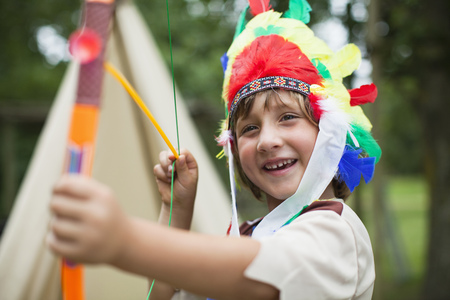 Boy with bow wearing Indian headdress