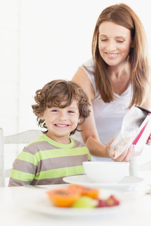 Mother pouring cereal for son
