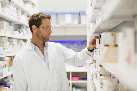 Pharmacist browsing medicines on shelf