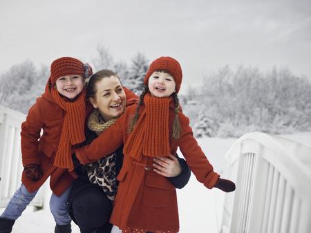 curare teneramente: Madre e figlie che giocano in neve