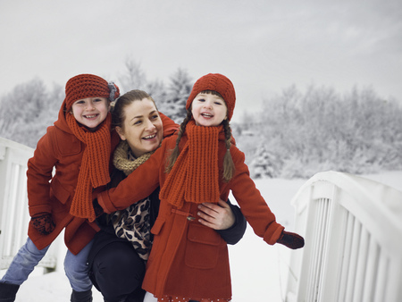 Mother and daughters playing in snow