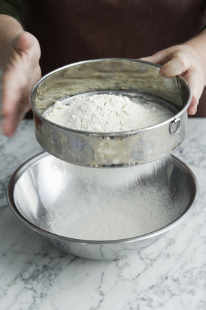 hits: Chef sifting flour in bowl