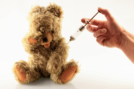appendages: Hand giving teddy bear a shot