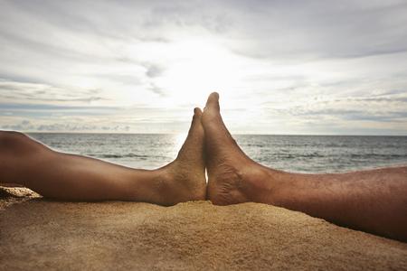 honeymooner: Close up of feet touching on beach