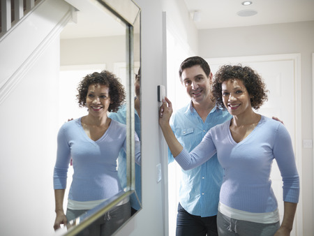 women's issues: Couple adjusting thermostat in home