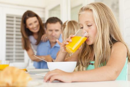 mornings: Girl drinking orange juice at breakfast