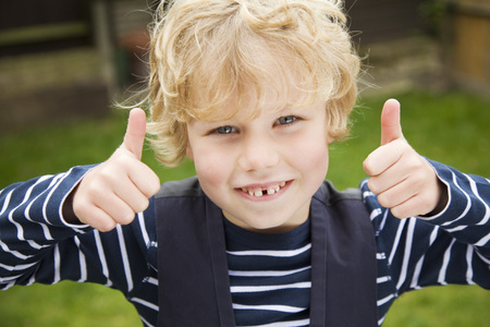 Smiling boy giving thumbs-up outdoors LANG_EVOIMAGES