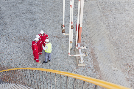 under control: Workers talking at chemical plant