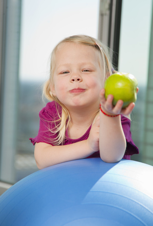 morsels: Girl eating apple on exercise ball