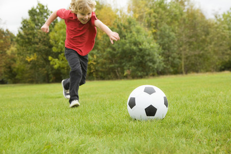 level playing field: Boy playing with soccer ball in field