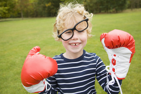 aggressively: Boy playing with boxing gloves outdoors