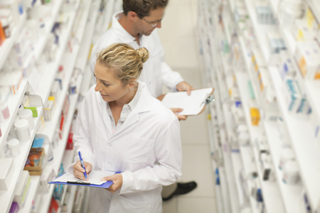 Pharmacists browsing medicines on shelf
