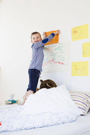 Boy hanging drawing on bedroom wall LANG_EVOIMAGES
