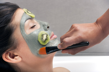 grooming: Woman having skin mask applied in bath LANG_EVOIMAGES