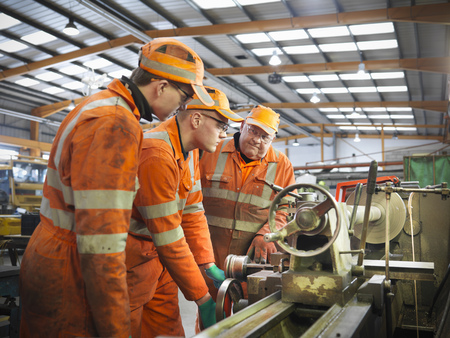 the elderly tutor: Engineer teaching apprentices in factory