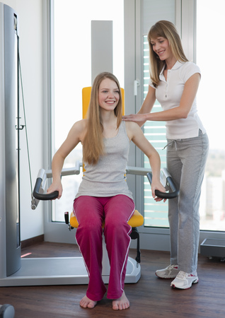 pubescent: Trainer working with girl in gym