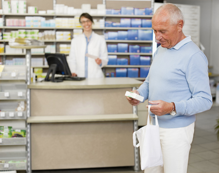 Man picking up prescription at pharmacy