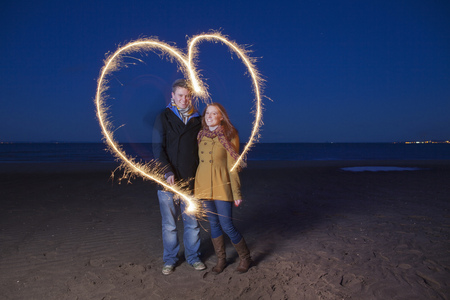 Couple playing with sparklers on beach