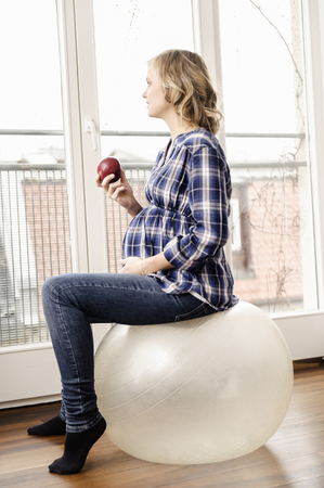 musing: Pregnant woman sitting on exercise ball