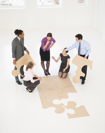 strategize: Business people doing puzzle in office