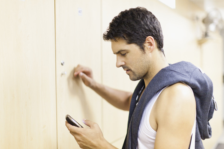 responded: Man using cell phone in locker room LANG_EVOIMAGES