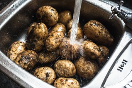 dirtied: Water rinsing potatoes in sink