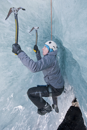 Climber climbing out of ice cave LANG_EVOIMAGES