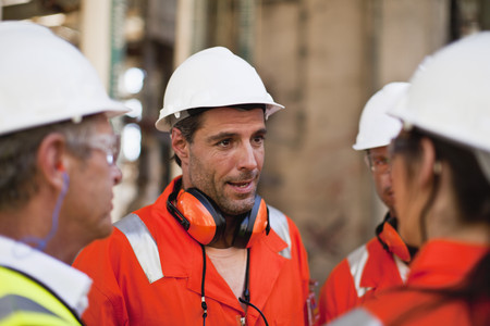 resolving: Workers talking at oil refinery LANG_EVOIMAGES