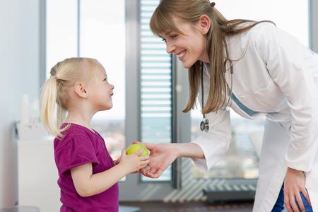 provide: Doctor handing girl an apple in office