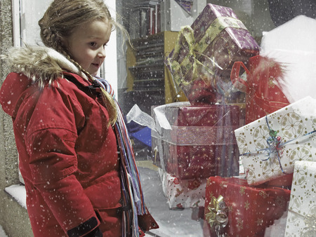 requiring: Girl admiring Christmas gifts in snow LANG_EVOIMAGES