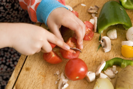 Close up of child slicing vegetables LANG_EVOIMAGES