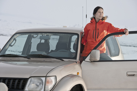 anorak: Woman climbing into car in snow